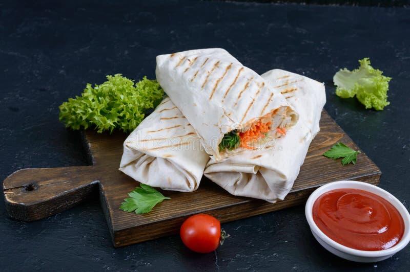 Очень вкусный сэндвич shawarma на черной предпосылке Обручи буррито с зажаренными цыпленком и овощами, зелеными цветами стоковое изображение