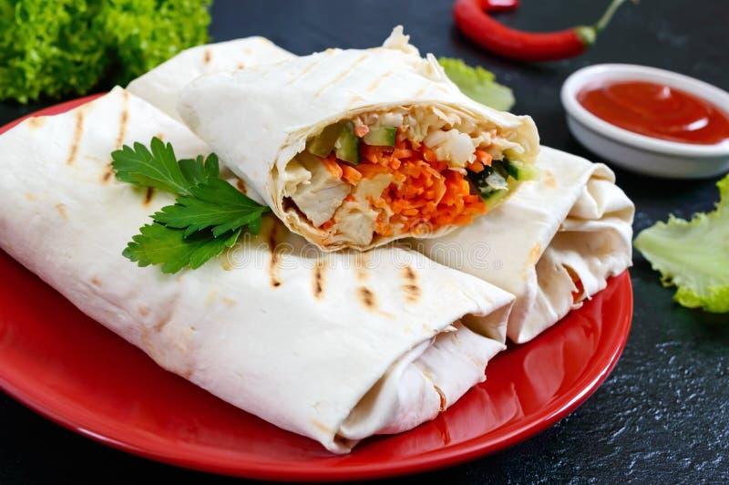 Очень вкусный сэндвич shawarma на черной предпосылке Обручи буррито с зажаренными цыпленком и овощами, зелеными цветами стоковые изображения rf
