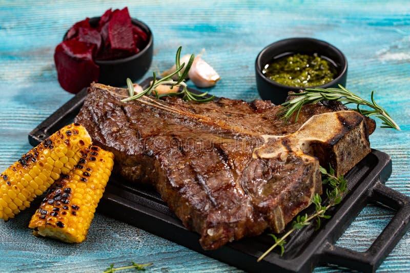 Очень вкусный стейк говядины на черной каменной разделочной доске Зажаренное мясо служило с зажаренной мозолью, чесноком, розмари стоковые фото