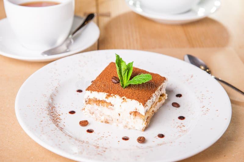 Очень вкусный торт тирамису с кофейными зернами и свежей мятой на плите на светлой деревянной предпосылке Селективный фокус, косм стоковая фотография
