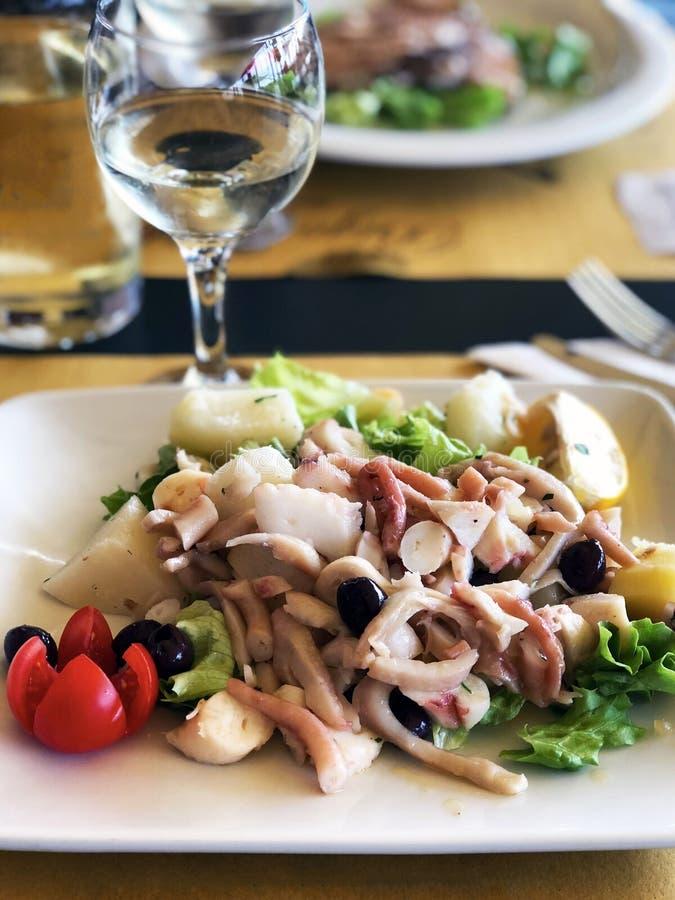 Очень вкусный романтичный обедающий: салат с кальмарами, осьминогом, оливками и зелеными цветами стоковые изображения rf