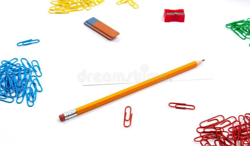Ołówek, gumka, ostrzarka, papierowe klamerki kłama w różnych kątach prześcieradło na białym tle Bohater kopii i wizerunku przestr obrazy royalty free