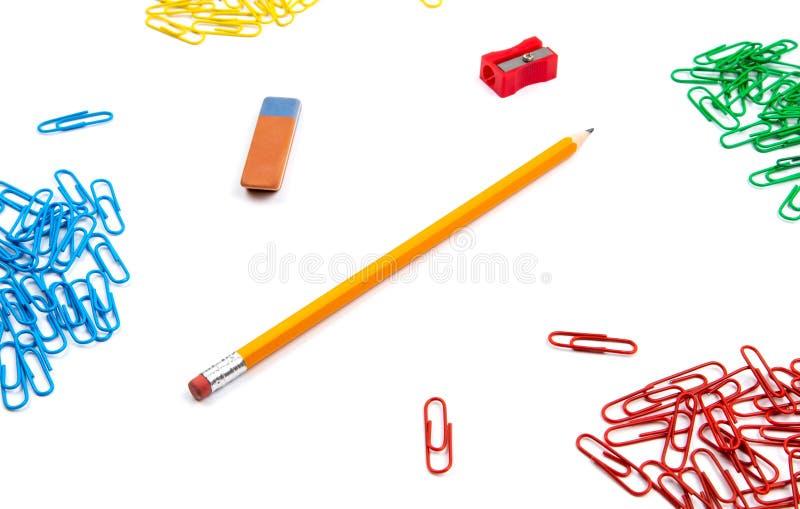Ołówek, gumka, ostrzarka, papierowe klamerki kłama w różnych kątach prześcieradło na białym tle Bohater kopii i wizerunku przestr zdjęcie stock