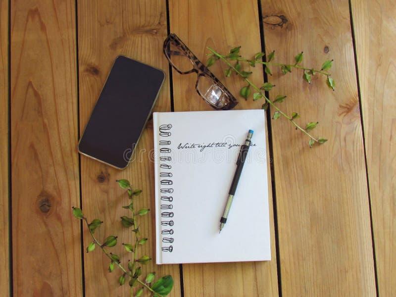 Ołówek na notatniku, szkłach i telefonie na drewnianej podłodze białych, zdjęcia royalty free