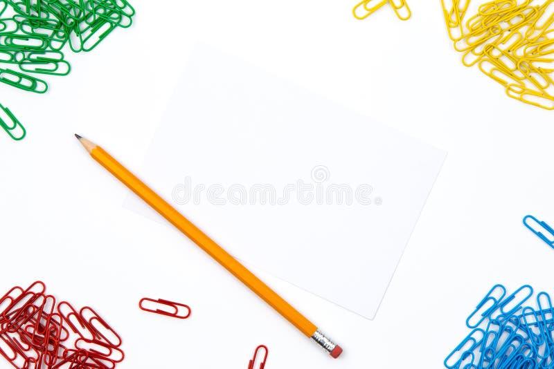 Ołówek, papierowe klamerki kłama w różnych kątach prześcieradło na białym tle Bohater kopii i wizerunku przestrzeń zdjęcia royalty free