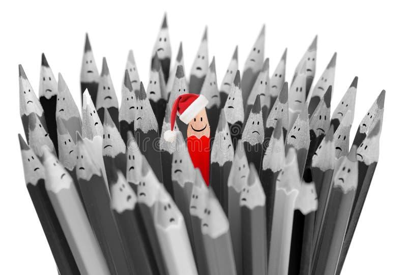 Ołówek z uśmiechem w Santa Bożenarodzeniowym kapeluszu wśród smutnej grupy zdjęcie stock