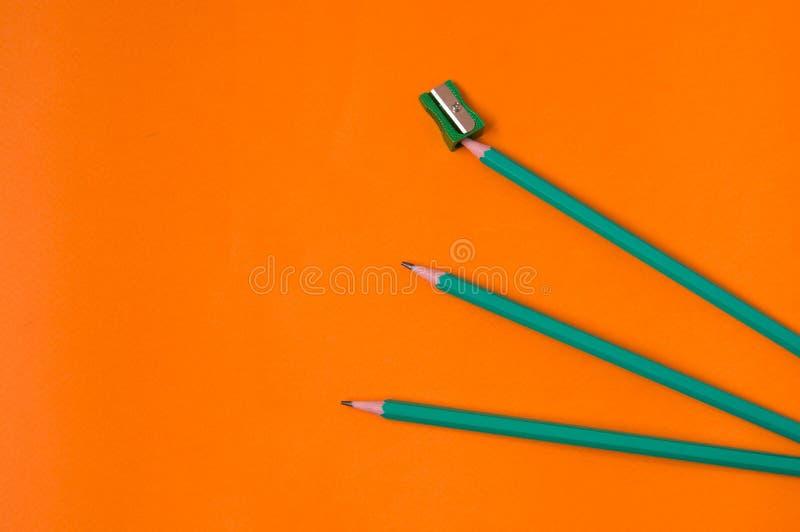 Ołówki i ostrzarka na pomarańczowym tle fotografia royalty free