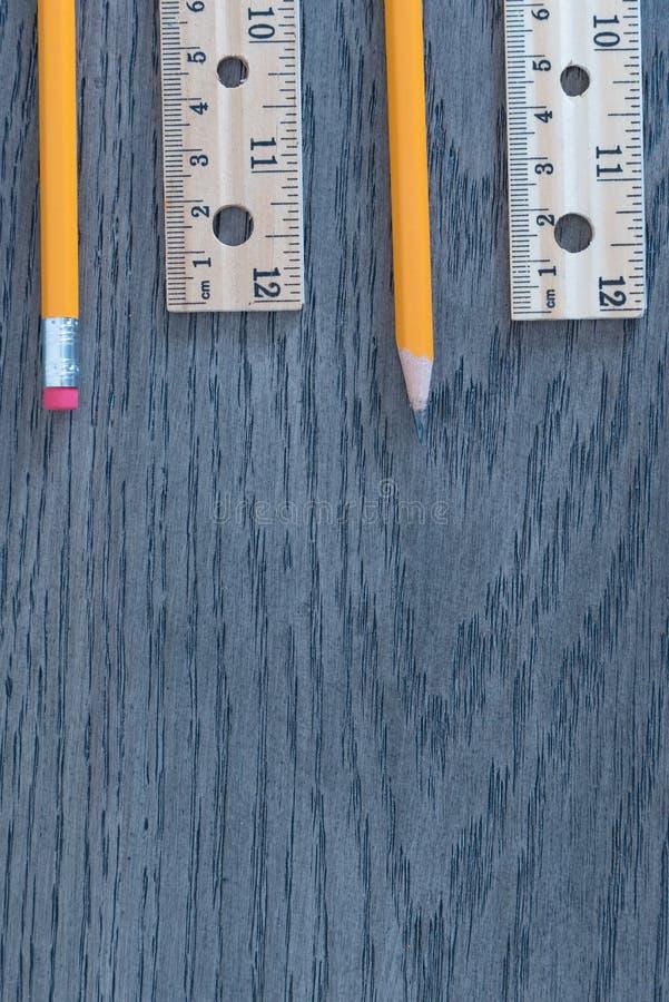 Ołówki i władcy na szarym drewno adry tła mieszkaniu kłaść przygotowania fotografia royalty free