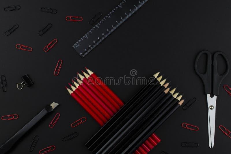Ołówki w czerni i czerwieni, władca, nożyce i przycinają kłamstwa na czarnym tle zdjęcia royalty free