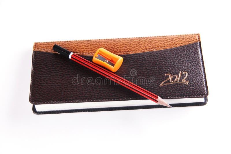 Ołówkowej ostrzarki i notatnika nabiał odizolowywający na białym tle obraz stock