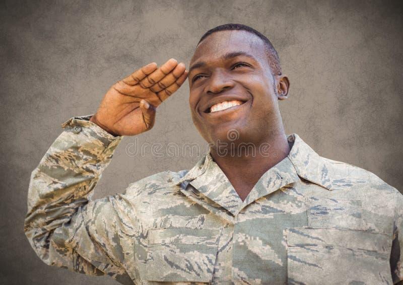 Żołnierz ono uśmiecha się i salutuje przeciw brown tłu z grunge narzutą obraz royalty free