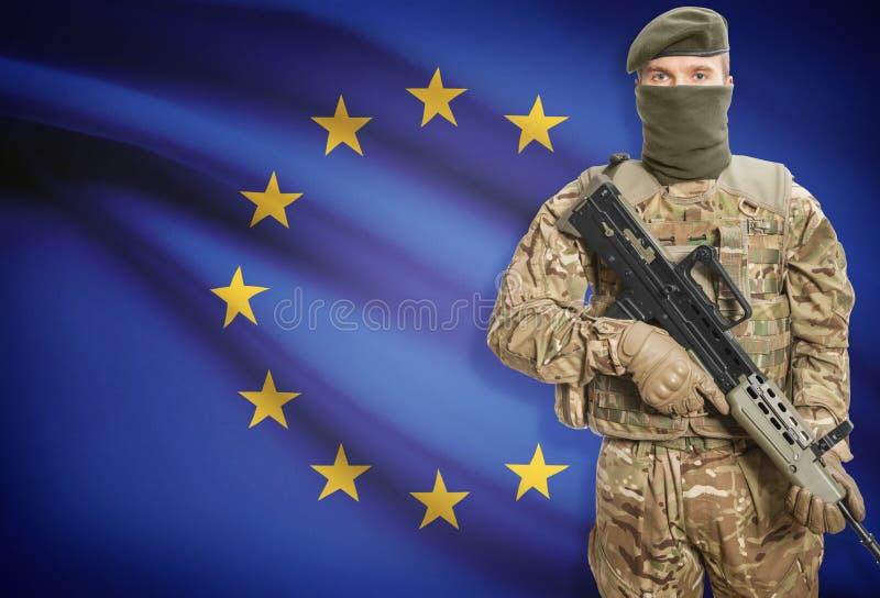 Żołnierz trzyma maszynowego pistolet z flaga na tło seriach UE - Europejski zjednoczenie - obrazy royalty free