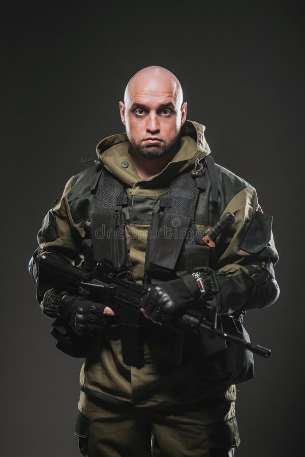 Żołnierza mężczyzna chwyta Maszynowy pistolet na ciemnym tle zdjęcia stock