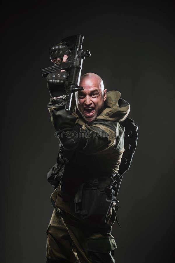 Żołnierza mężczyzna chwyta Maszynowy pistolet na ciemnym tle fotografia royalty free