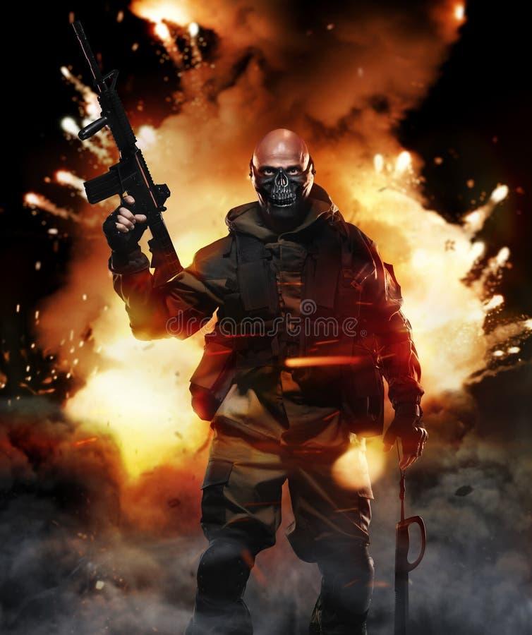 Żołnierza mężczyzna chwyta Maszynowy pistolet na tle wybuch zdjęcie stock