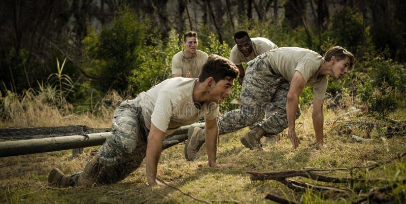 Żołnierze czołgać się pod siecią podczas przeszkoda kursu obraz royalty free