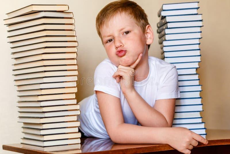 Ośmioletnia chłopiec w białej koszulce i mnóstwo książkach na stole fotografia stock