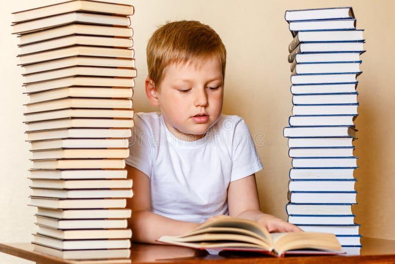 Ośmioletnia Kaukaska chłopiec czyta książkę w białej koszulce, siedzi przy stołem obraz royalty free