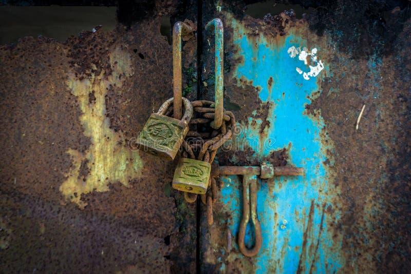 Ośniedziałe kłódki z łańcuchami wciąż blokuje bramę z błękitną colour fotografią brać w Dżakarta Indonezja obraz stock