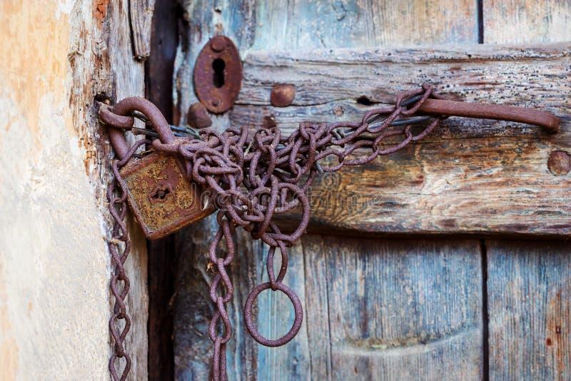 Ośniedziały drzwiowy kędziorek i łańcuch na starym drzwi obraz royalty free