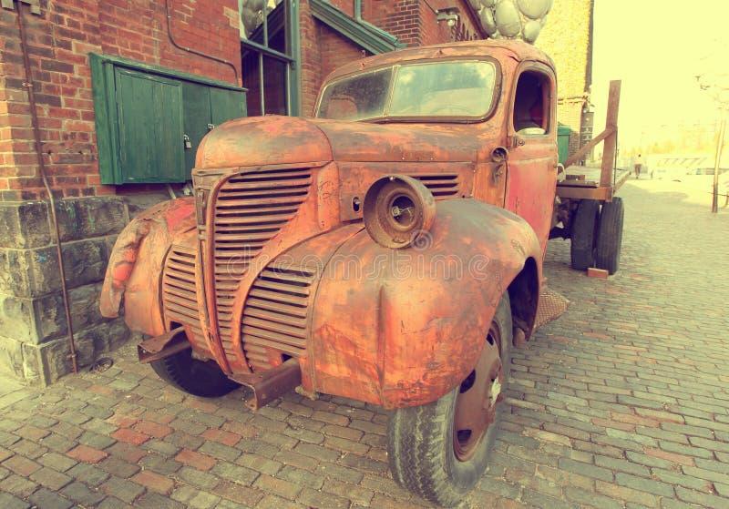 Ośniedziały grille stara czerwieni ciężarówka parkująca na ulicznym retro starym samochodzie obraz stock