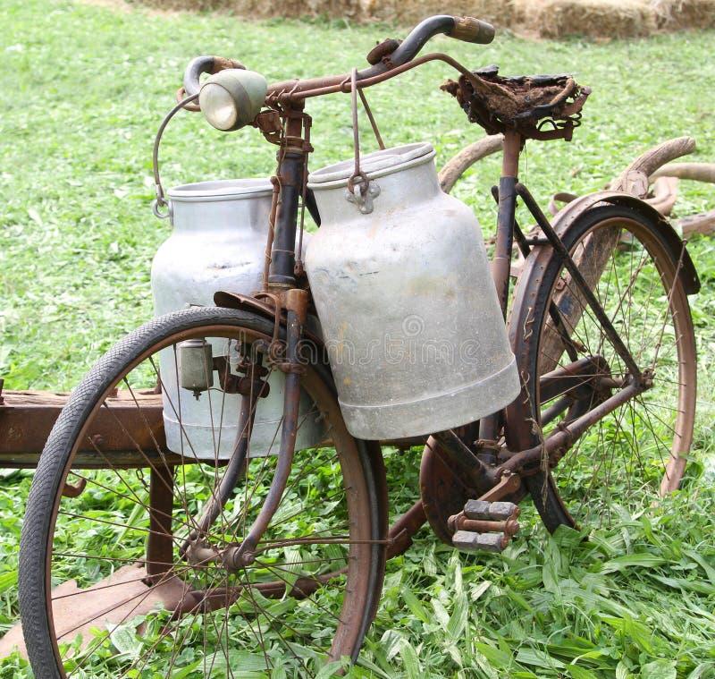 Ośniedziały stary rower milkman z dwa starymi dojnymi puszkami i łamający zdjęcia royalty free