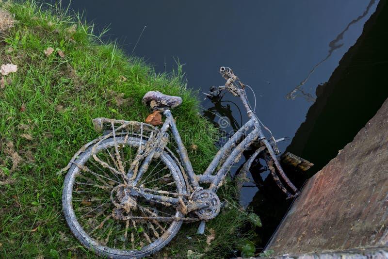 Ośniedziały stary rowerowy lying on the beach porzucający na polu, wzdłuż wody fotografia royalty free