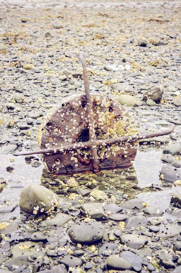 Ośniedziały statku silnik na skalistej plaży obraz royalty free