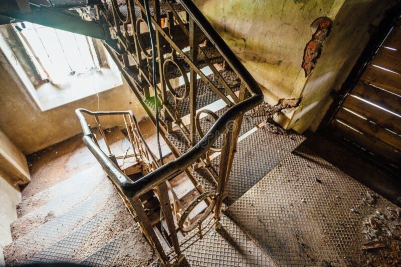 Ośniedziali żelazni schodki w starym zaniechanym dworze obraz stock