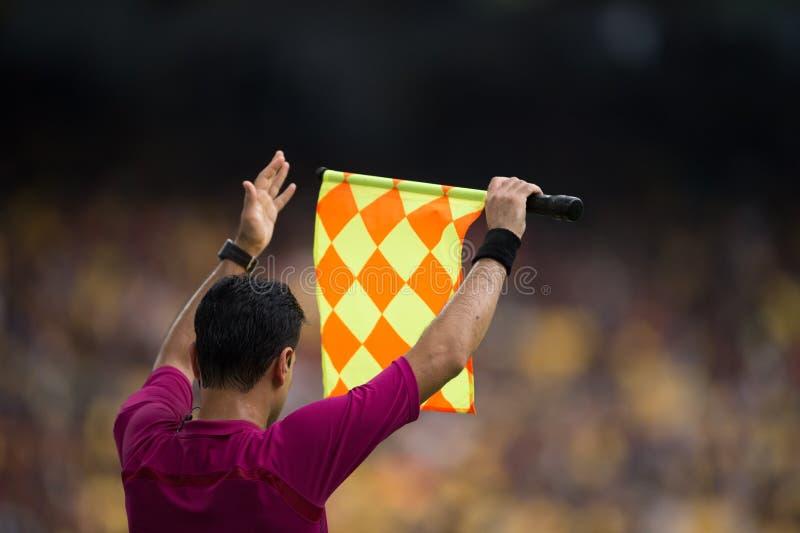 O árbitro assistente envia o sinal do jogador da substituição foto de stock