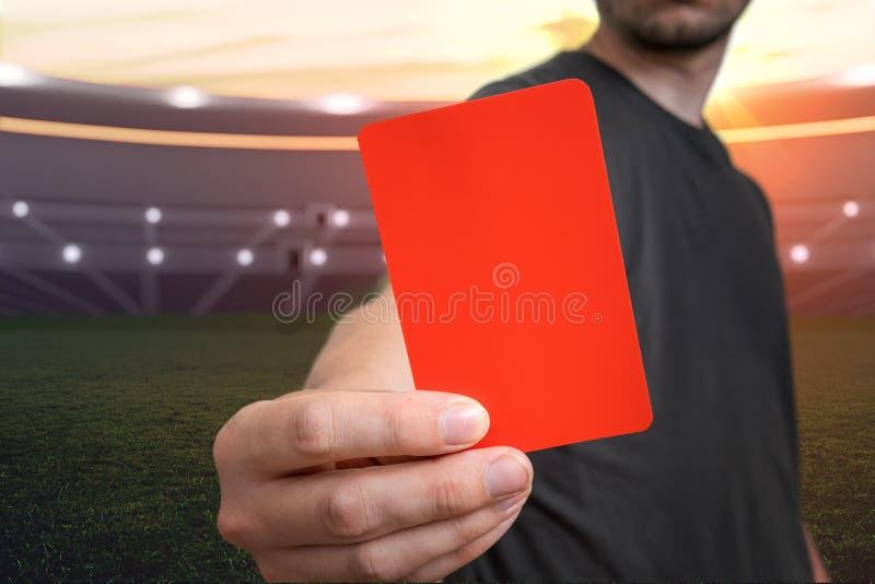 O árbitro está mostrando o cartão vermelho como uma pena para uma falta no estádio de futebol fotos de stock royalty free