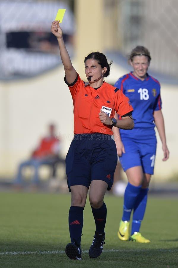 O árbitro fêmea do futebol, Riem Hussein mostra o cartão amarelo imagens de stock