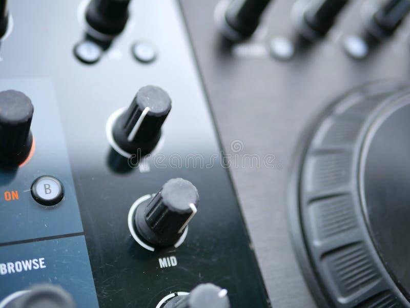 O áudio digital eletrônico DJ da música de dança alinha com botões, faders, em um festival do edm imagem de stock