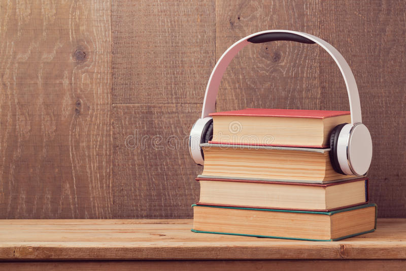 O áudio registra o conceito com a pilha de livro velho e de fones de ouvido na tabela de madeira foto de stock
