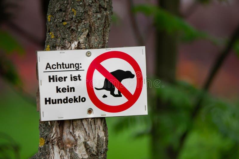 """O """"attention do sinal da proibição isto não é nenhum cão que o toilet"""" no alemão parafusou em uma árvore em um parque fotos de stock royalty free"""