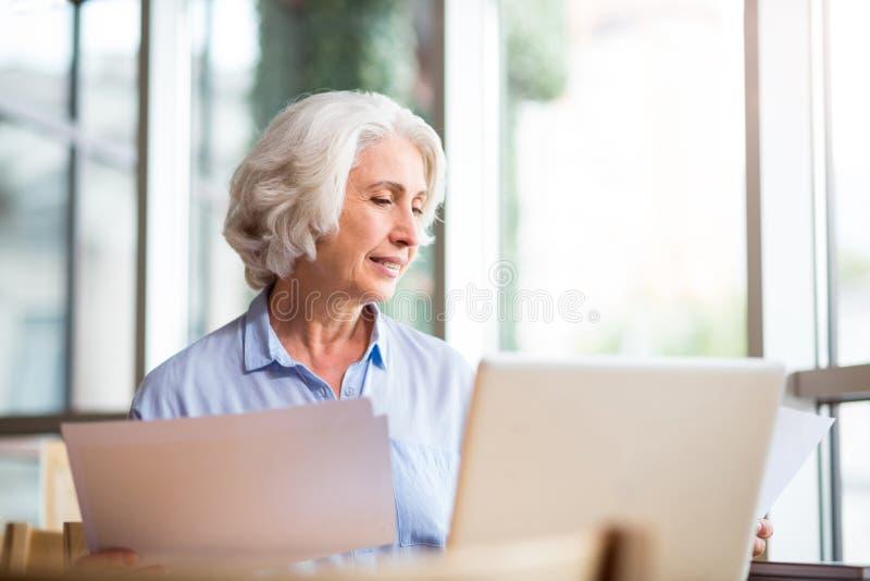 O índice agradável envelheceu a mulher que senta-se no café imagem de stock