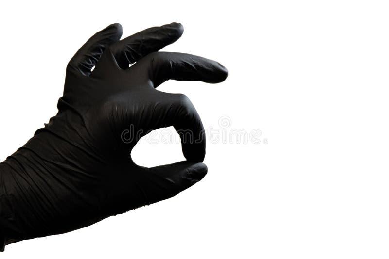 O índice e os polegares da mão esquerda na luva preta são dobrados sob a forma de um símbolo APROVADO em um fundo branco Isolado  imagem de stock royalty free