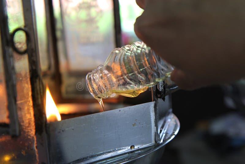 O óleo preenche uma lâmpada para iluminar-se e para o uso no incenso fotografia de stock royalty free
