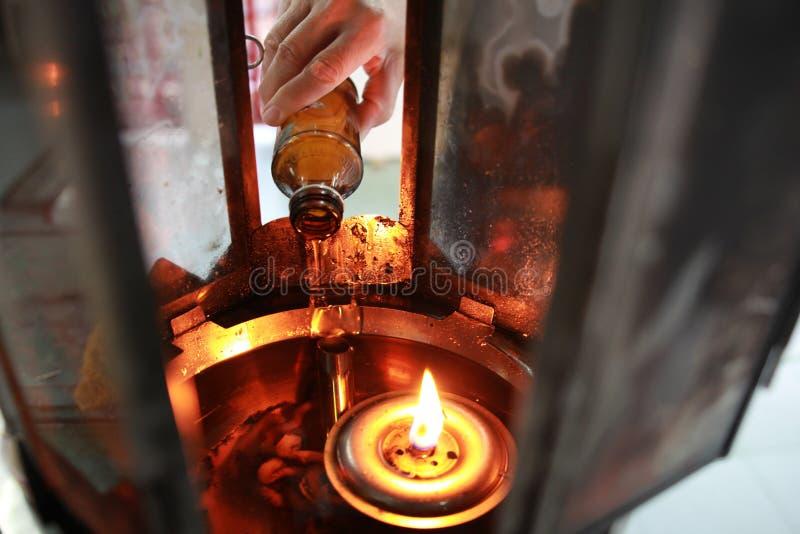 O óleo preenche uma lâmpada para iluminar-se e para o uso no incenso imagens de stock royalty free