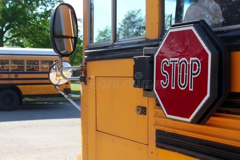 O ônibus escolar amarelo com sinal da parada fotografia de stock