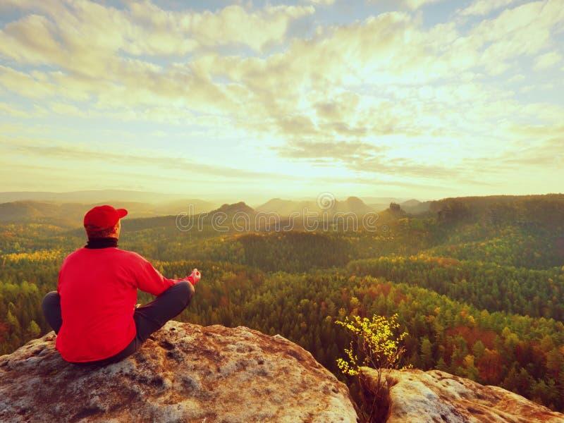 O único turista do homem senta-se no império da rocha Ponto de vista com pico rochoso exposto acima do vale imagens de stock