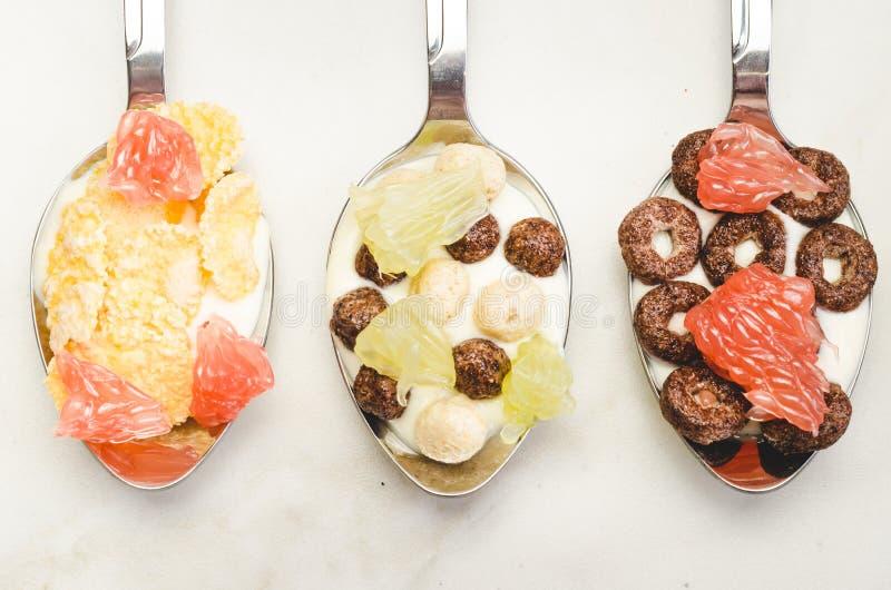 o Γιαούρτι, νιφάδες και φρούτα στα κουτάλια Τοπ άποψη, flatlay στοκ φωτογραφίες