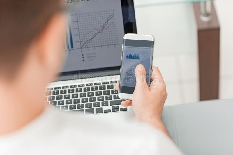 o επιχειρηματίας που χρησιμοποιεί τις συσκευές για το λογιστικό έλεγχο της οικονομικής έκθεσης στοκ φωτογραφίες