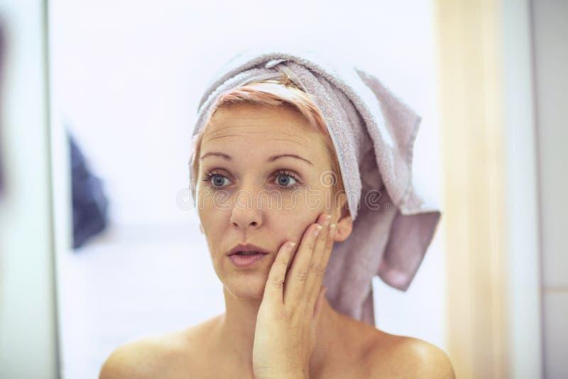 o η γυναίκα ανησυχεί για τις ρυτίδες στο πρόσωπό της στοκ φωτογραφία με δικαίωμα ελεύθερης χρήσης