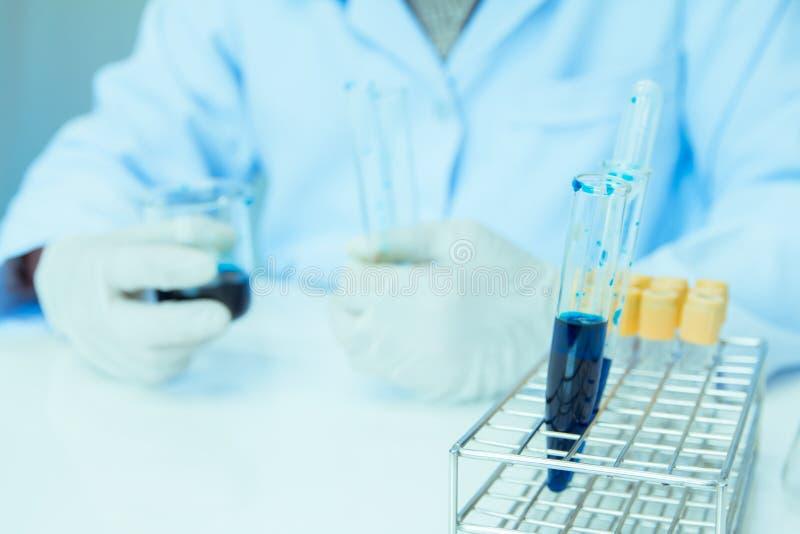 o Ιατρικός ή αρσενικός ιατρικός, κρατώντας την κούπα σωλήνων στην έρευνα εργαστηριακών δωματίων εκτελεί τις δοκιμές με το μπλε υγ στοκ φωτογραφίες