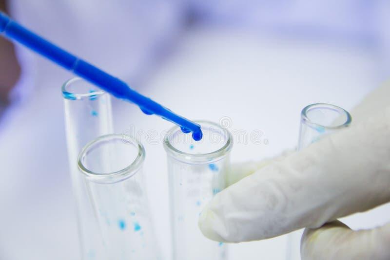 o Ιατρικός ή αρσενικός ιατρικός στην έρευνα εργαστηριακών δωματίων εκτελεί τις δοκιμές με το μπλε υγρό στοκ εικόνα με δικαίωμα ελεύθερης χρήσης