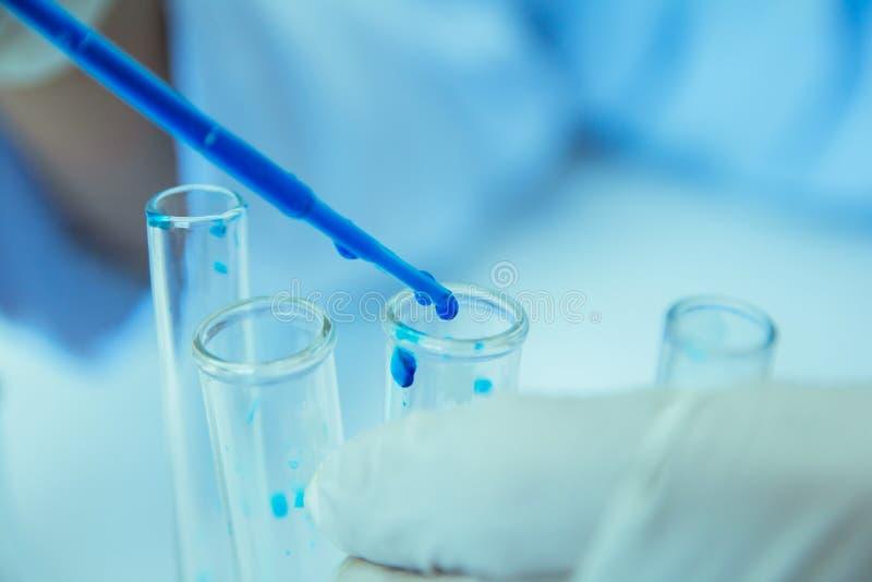 o Ιατρικός ή αρσενικός ιατρικός στην έρευνα εργαστηριακών δωματίων εκτελεί τις δοκιμές με το μπλε υγρό στοκ φωτογραφία με δικαίωμα ελεύθερης χρήσης