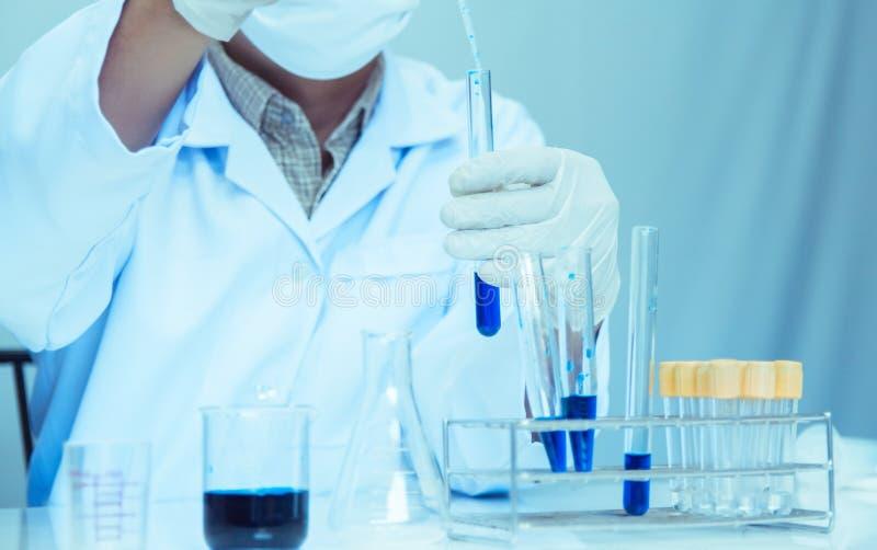 o Ιατρικός ή αρσενικός ιατρικός στην έρευνα εργαστηριακών δωματίων εκτελεί τις δοκιμές με το μπλε υγρό στοκ εικόνες