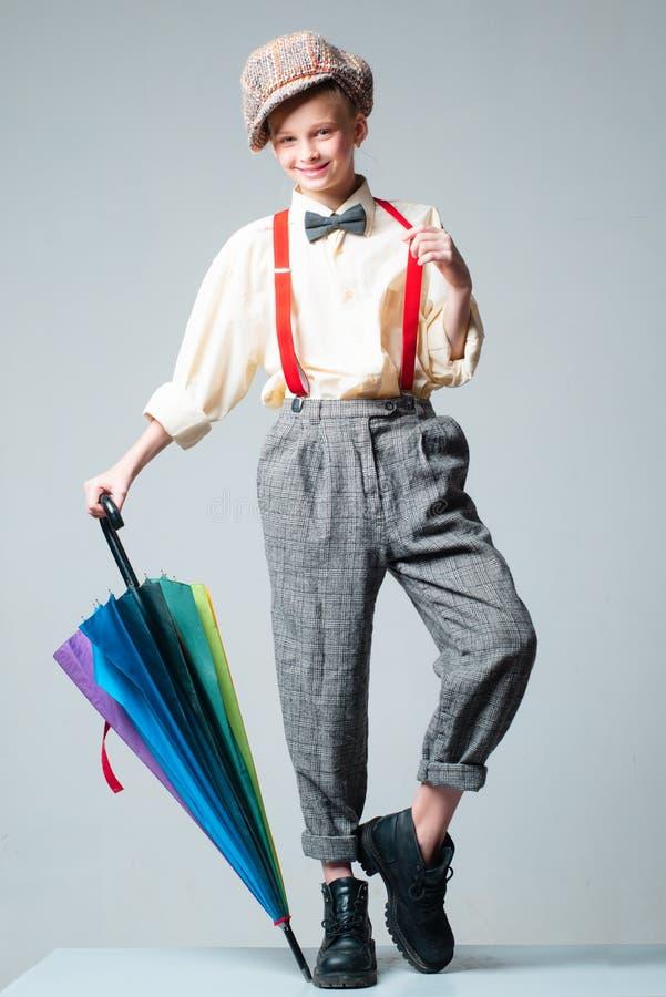 o o κορίτσι εφήβων στο αναδρομικό κοστούμι με την ομπρέλα suspender και τόξων δεσμός ντεμοντέ παιδί μέσα στοκ φωτογραφίες
