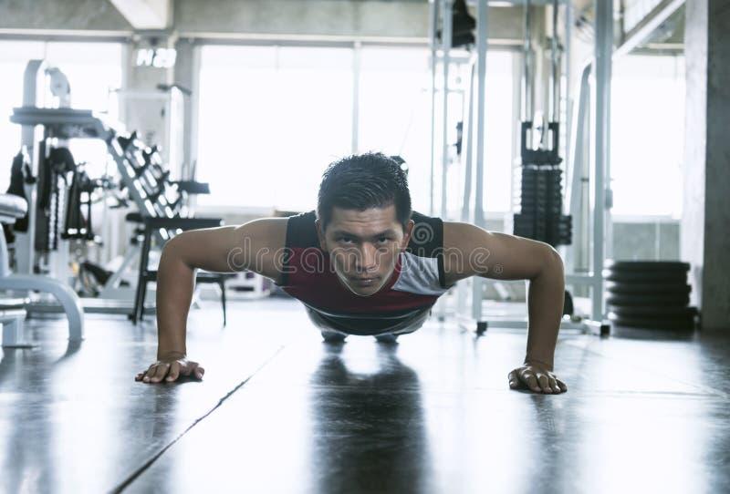 o Νέο ασιατικό αθλητικό άτομο που κάνει ώθηση-επάνω στη μυϊκή άσκηση στη γυμναστική ικανότητας στοκ εικόνες